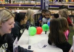Children work on a science experiment with balloons
