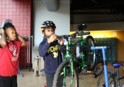 A boy works on fixing a bike