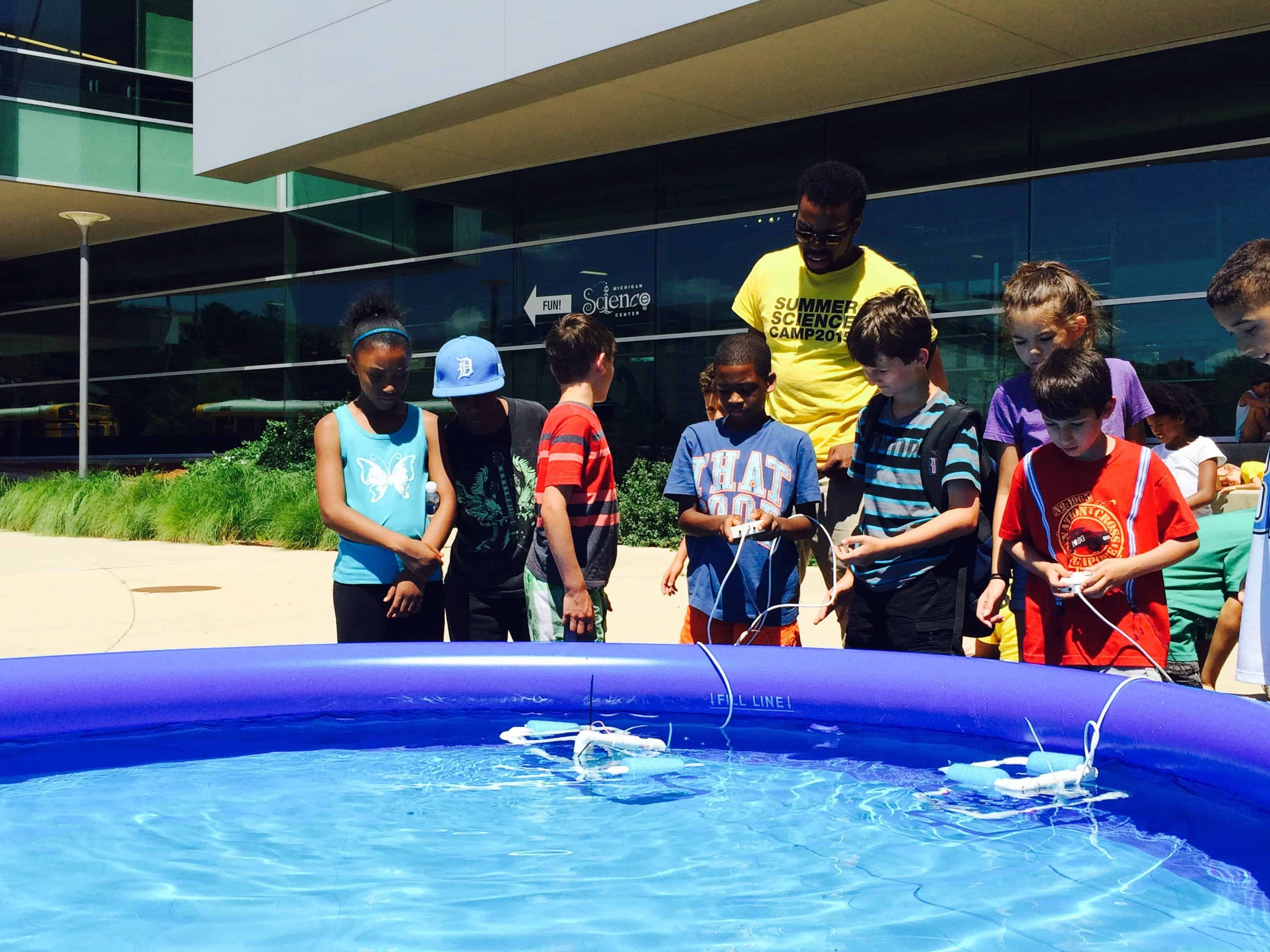 A Science Center educator and summer campers test their underwater robots in a small pool