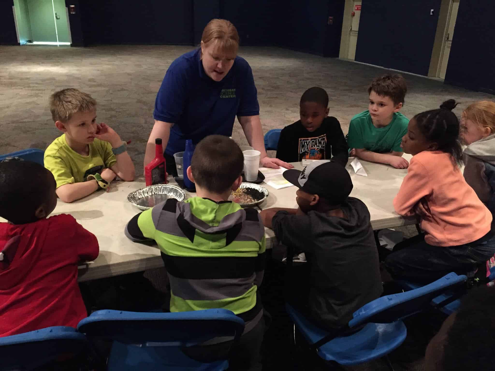 A science center educator teaches a group of children during summer camp