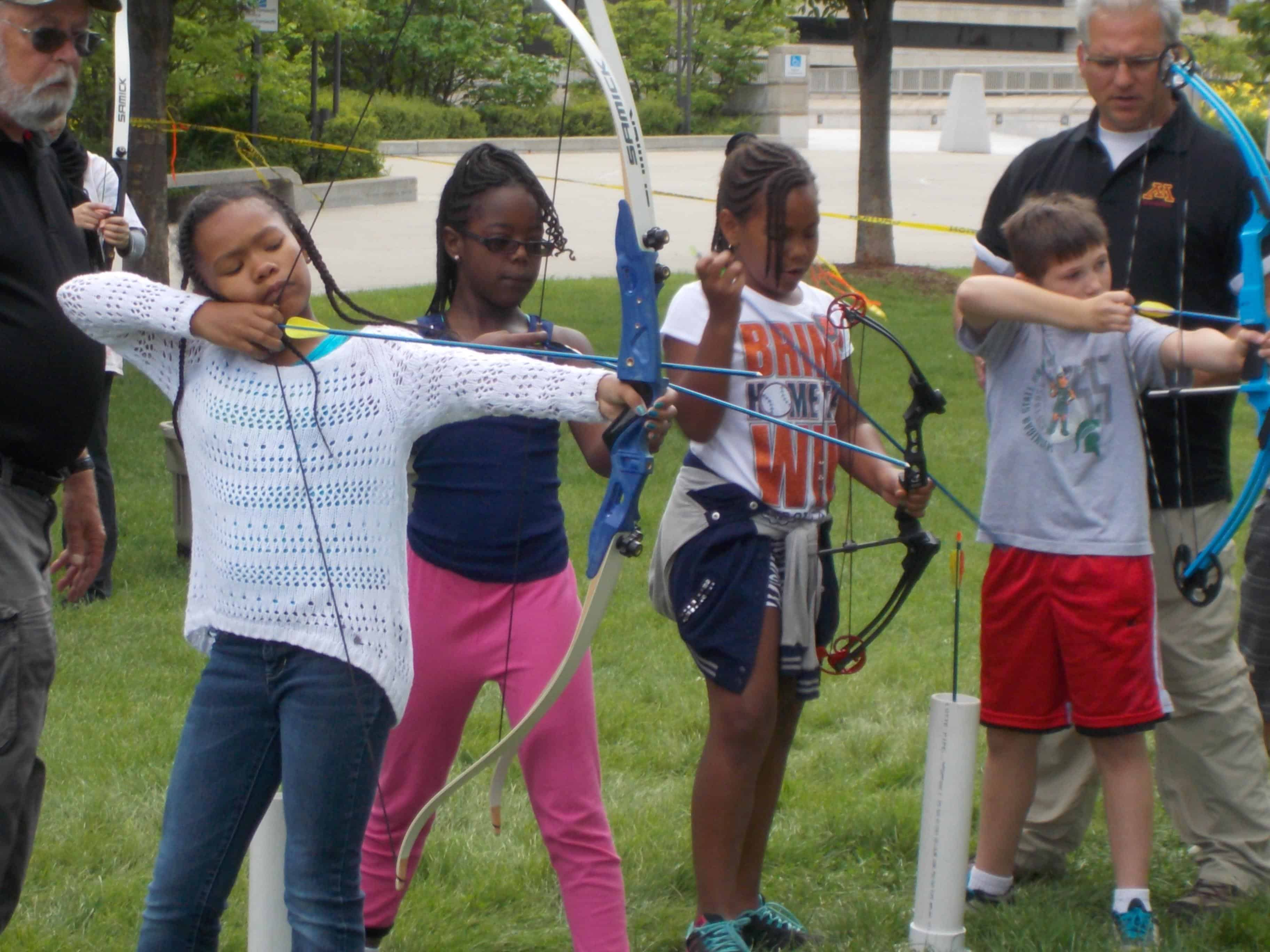 A group of children hold bows and arrows as they learn about survival during summer camp