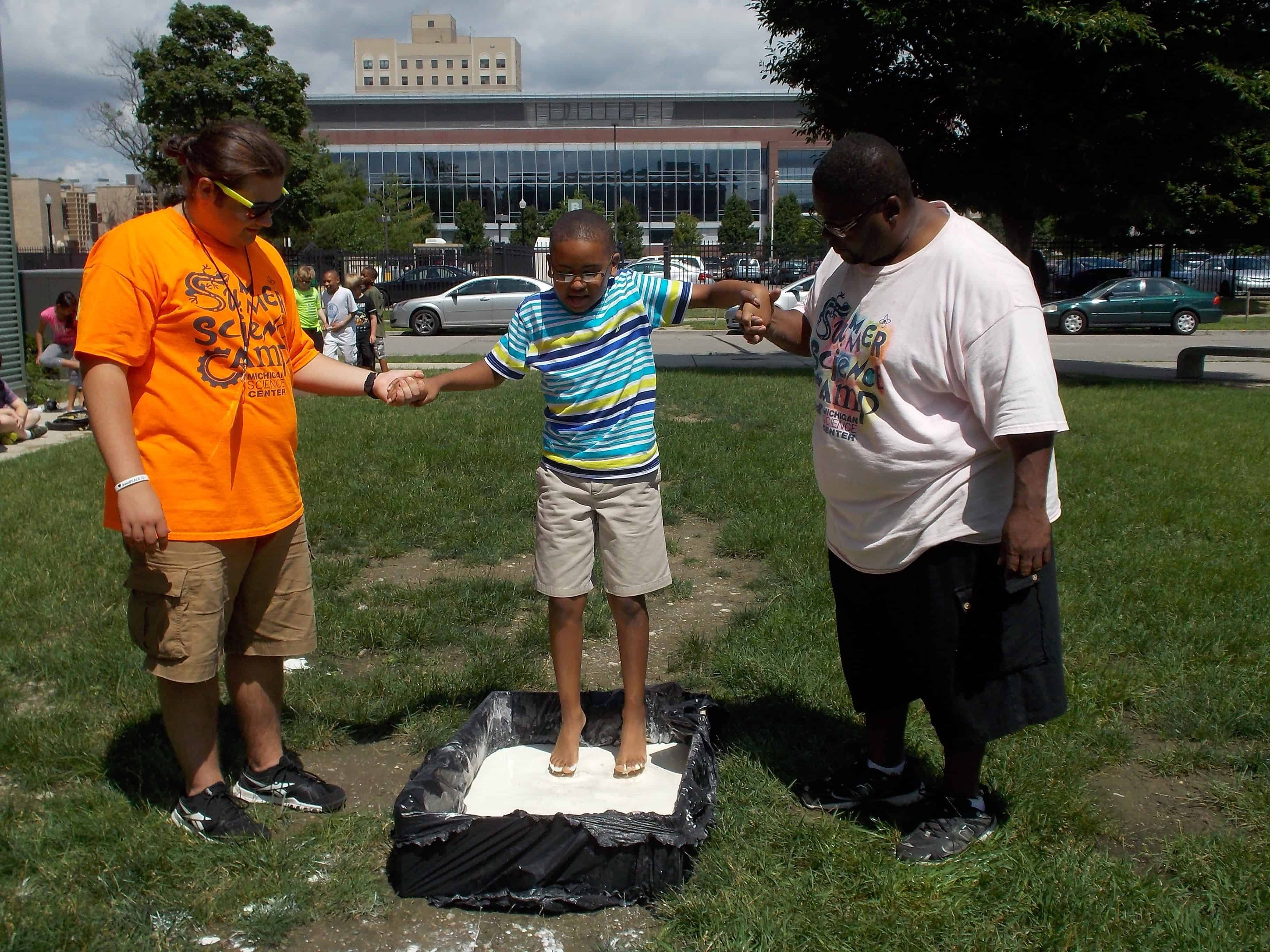 Two Science Center educators help a camper step into oobleck - an example of a non-newtonian fluid
