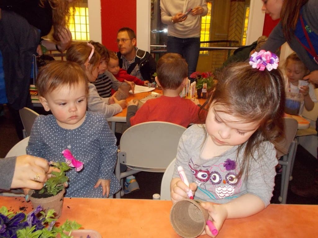 Two children plant flowers as they learn about nature