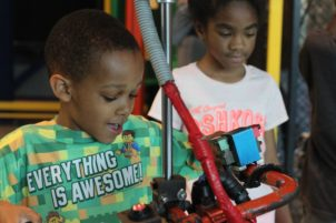 Two children use a manufacturing exhibit