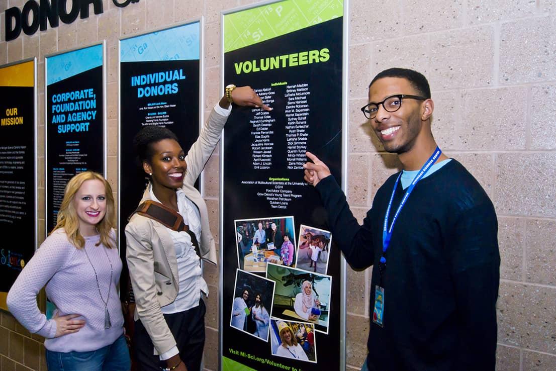 Volunteers find their names on the Volunteers wall!