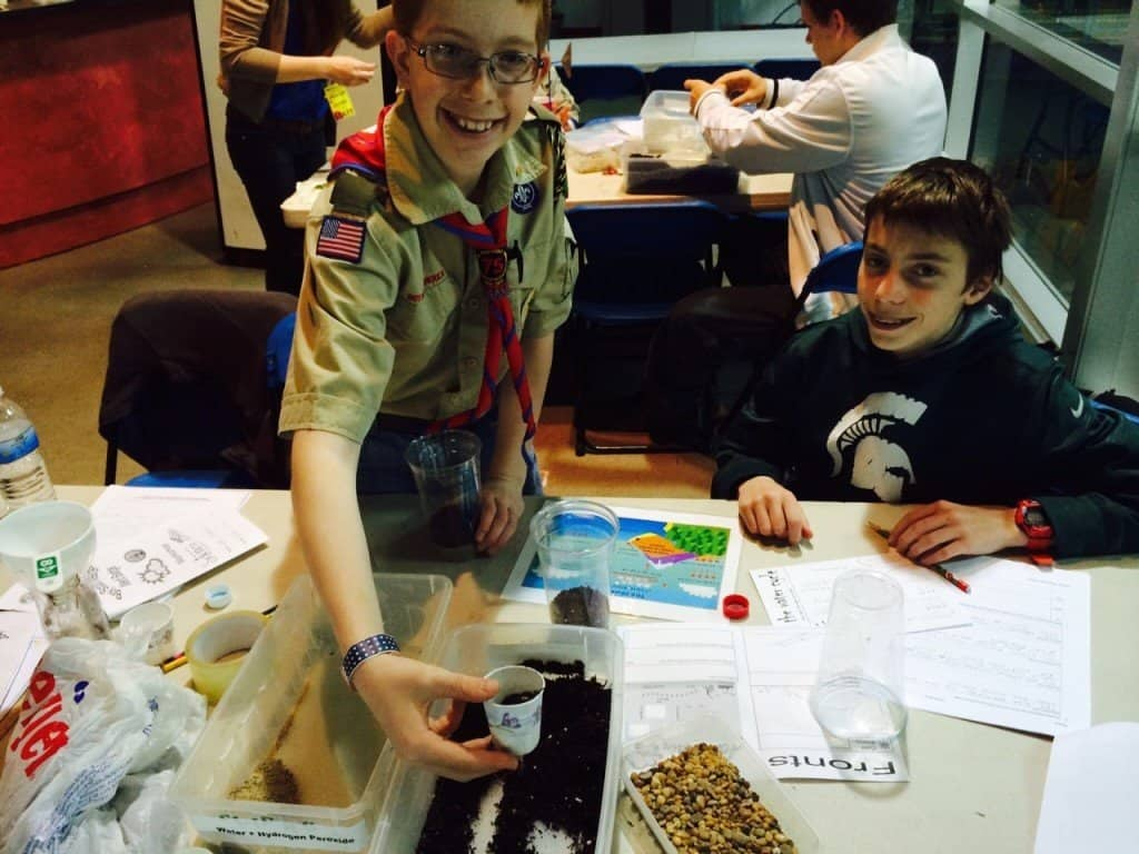 Two boy scouts complete an activity to learn about the water cycle