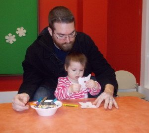 A father and daughter complete a craft in Kids Town