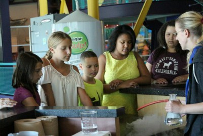 A group of children listen to a presentation from a science center educator