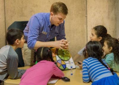 An educator talks with children in the Michigan Science Center's Spark Lab