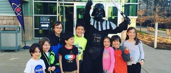 Guests pose with Darth Vader from the Star Wars movies