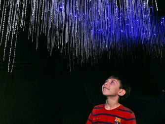 A boy looks up at models of glow worms