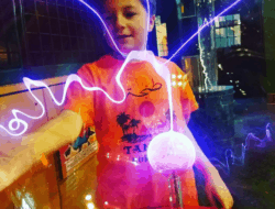 A young boy experiments with a plasma globe
