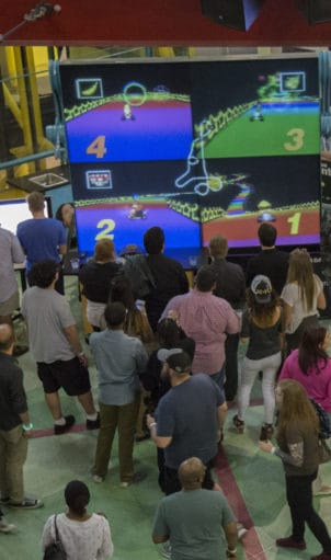 Guests play video games on a giant screen.