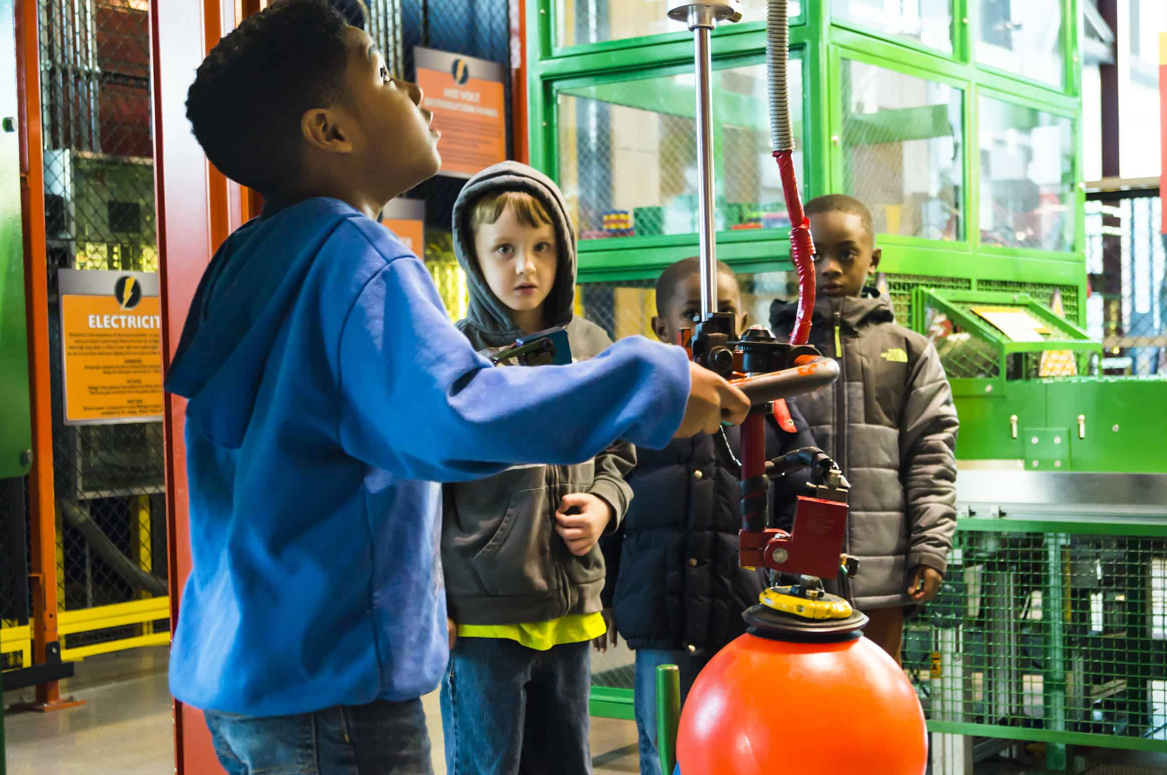 Three children use a suction lift exhibit in the Fun Factory space