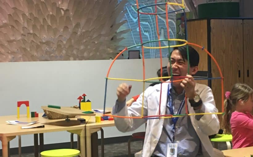 Volunteer of the Month Colin Anderson holds a plastic structure in Spark!Lab